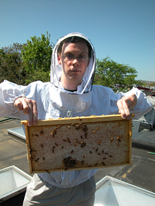 Etienne James Hunter Pollard holds honey frame